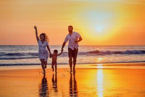 a photo of a happy family walking in the beach during sunset