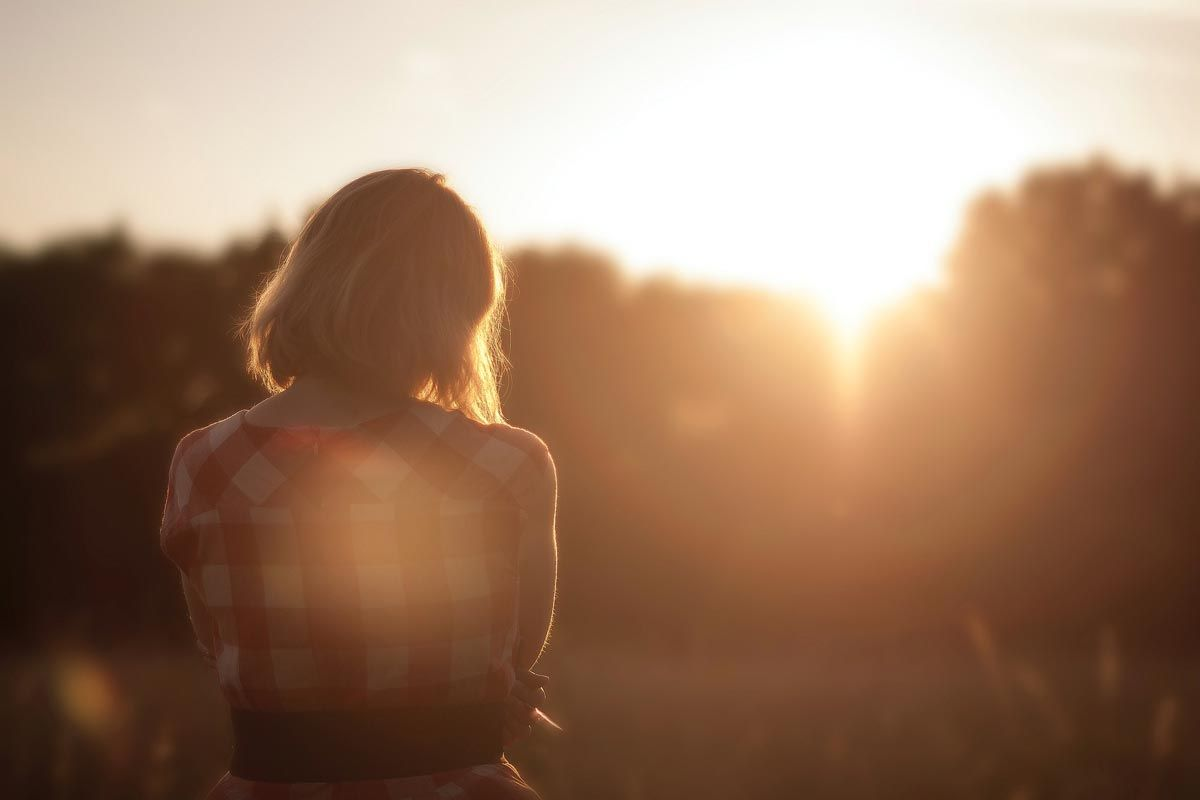 photo of a sad christian woman standing outdoor during sunset